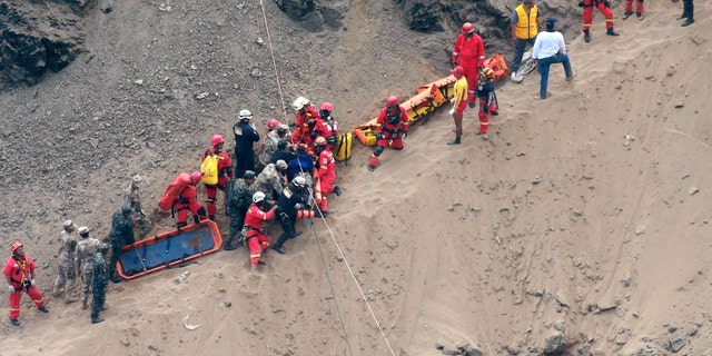 Rescue workers surround an injured man on a stretcher who was lifted up from the crash site on the beach.