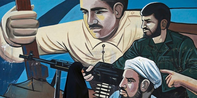 Jan 3: A woman walks past of a mural depicting members of Iran's Basij volunteer paramilitary force, in downtown Tehran