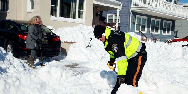 A Longport Police Officer helps a resident shovel her driveway in Longport, N.J.