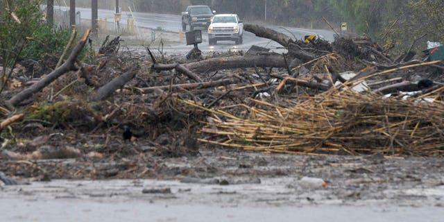 Debris from a swollen creek blocks Via Real in Carpinteria, California.