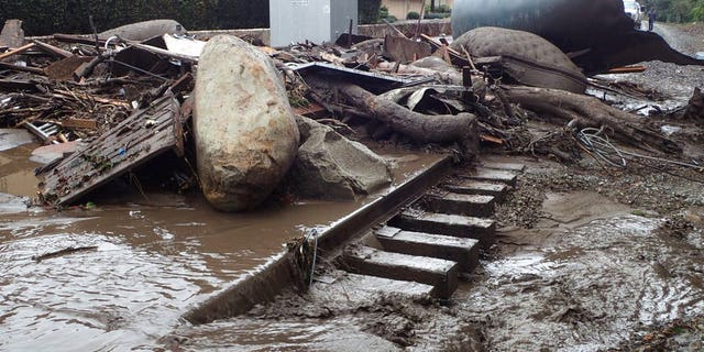 In this photo provided by Santa Barbara County Fire Department, the main line of the Union Pacific Railroad through Montecito, California is blocked with mudflow and debris due to heavy rains