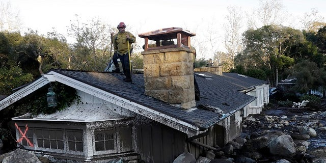 A firefighter stands on the roof of a house submerged in mud and rocks Wednesday, Jan. 10, 2018, in Montecito, Calif.