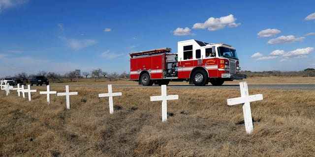 Ryland Ward looks out the passenger window as he passes a memorial of crosses as he returns home after his release from the hospital while riding in the cab of a firetruck on Jan. 11, in Sutherland Springs, Texas.