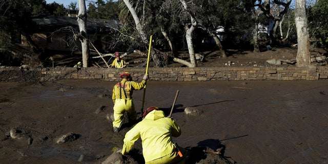 A Cal Fire search and rescue crew walks through mud near homes damaged by storms in Montecito, Calif., on Friday.