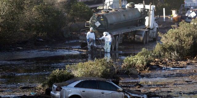 Crews pump mud on Highway 101 after a mudslide Saturday in Montecito, Calif.