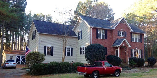 Cars are parked at a home in York, S.C. on Tuesday where multiple deputies responding to a domestic violence call were shot and wounded.