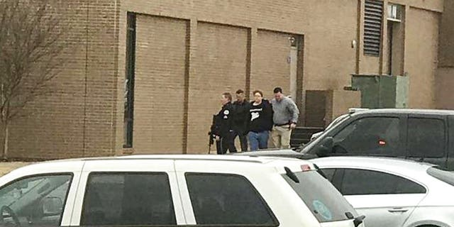 olice escort a person, second from right, out of the Marshall County High School after shooting there, Tuesday, Jan 23, 2018, in Benton, Ky.