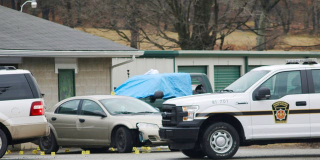 Evidence markers sit on the scene of a fatal shooting at a car wash in Melcroft, Pa., Sunday, Jan. 28, 2018.