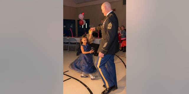 Cayleigh Hinton, daughter of Army Sgt. Terrence Hinton, dances with 1st Sgt. Joseph Bierbrodt of Sheridan, Ill., with the 933rd Military Police Company, at a father-daughter dance held at the Our Lady of Humility School