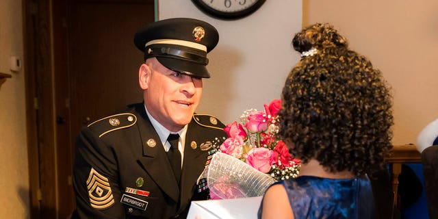 1st Sgt. Joseph Bierbrodt of Sheridan, Ill., with the 933rd Military Police Company, asks Cayleigh Hinton if he can escort her to the father-daughter dance at the Our Lady of Humility School