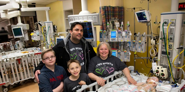 Parents Jill and Michael Richards along with their two sons, Collin and Seth, stand in the recovery room on Jan. 13 by the two beds after their twin conjoined daughters, Anna and Hope, were successfully separated.