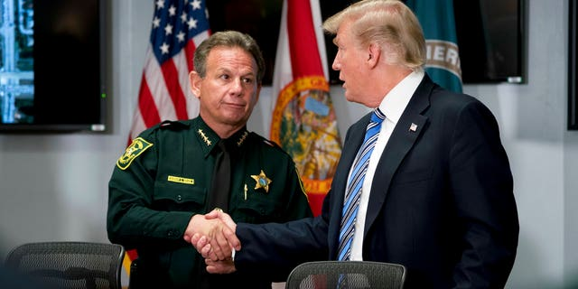 Broward County Sheriff Scott Israel, pictured here with President Trump, said that as of Feb. 21, all county schools will have deputies, armed with rifles, patrolling campus.