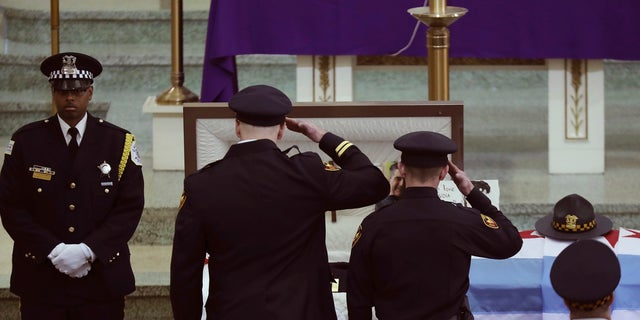 Two officers salute Chicago police Commander Paul Bauer before his funeral mass at Nativity of Our Lord Roman Catholic Church on Saturday in Chicago.