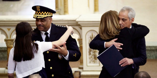 Chicago police Superintendent Eddie Johnson hugs Grace Bauer, 13, as Mayor Rahm Emanuel hugs Erin Bauer during the funeral Mass of Chicago police Cmdr. Paul Bauer on Saturday in Chicago.