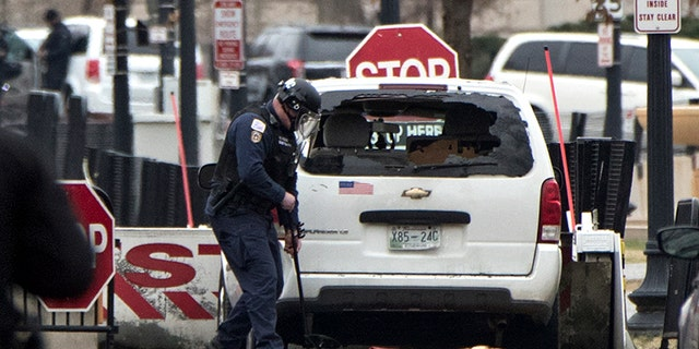 A Secret Service officer checks a white passenger vehicle that struck a security barrier guarding the southwest entrance to the White House grounds off of 17th Street n Washington on Friday.