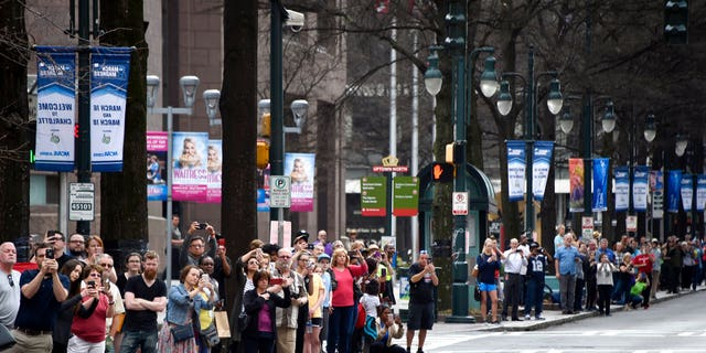 People line the street to watch the casket carrying the body of Billy Graham travel through Charlotte, N.C.