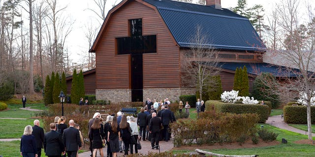 Pall bearers carry the caskey carrying the body of Billy Graham as family members follow behind to the Billy Graham Library in Charlotte, North Carolina on Saturday.