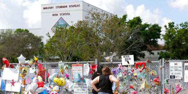 Mourners pay tribute at a memorial for the victims of the shooting at Marjory Stoneman Douglas High School on Sunday, Feb. 25, 2018, in Parkland, Fla.