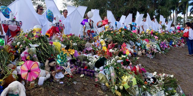 Seventeen people dressed as angels stand Sunday, Feb. 25, 2018, at the memorial outside Marjory Stoneman Douglas High School in Parkland, Fla., for those killed in a shooting on Feb. 14.