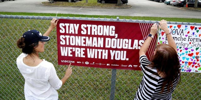 Volunteers hang banners around the perimeter of Marjory Stoneman High School in Parkland, Fla., to welcome back students who will be returning to school Wednesday two weeks after the mass shooting that killed 17 students and staff. (Associated Press)