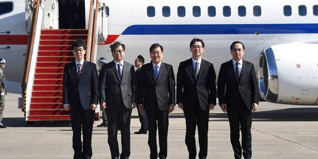 South Korea's national security director Chung Eui-yong, center, National Intelligence Service Chief Suh Hoon, second left, and other delegators pose before boarding an aircraft as they leave for Pyongyang at a military airport in Seongnam, south of Seoul, Monday, March 5, 2018.