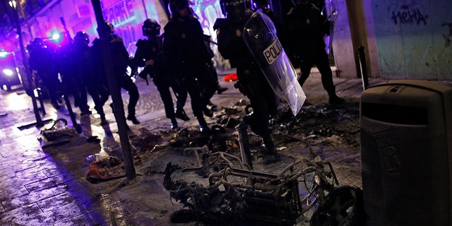 Protesters lit parked vehicles and trash cans on fire during clashes with Madrid police.
