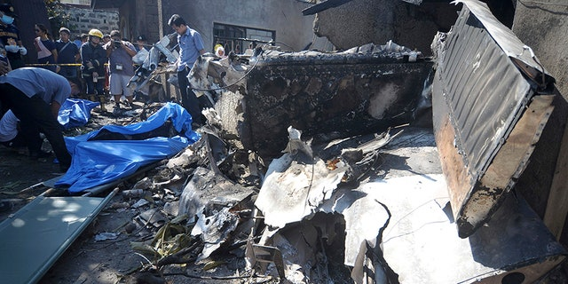 The burnt wreckage of a Piper PA-23 Apache six-seater twin-engine light aircraft is seen at right as rescuers recover the bodies of victims following a crash upon takeoff Saturday.