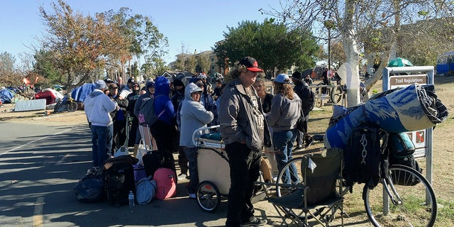 Homeless people line up in preparation to move from their homeless camp site along a riverbed.