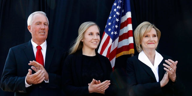 Cindy Hyde-Smith (right) stands with her husband, Mike Smith (left) and daughter Anna-Michael Smith (center) as the governor announces her appointment to the U.S. Senate.