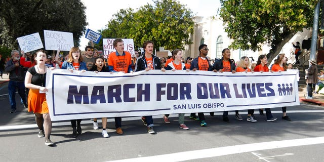 People participate in a March for Our Lives event, Saturday, March 24, 2018, in San Luis Obispo, Calif.