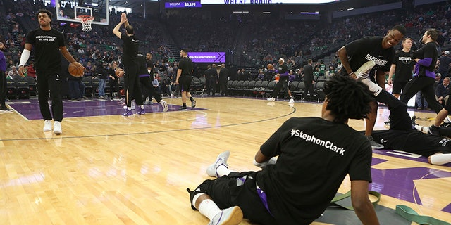 Sacramento Kings guard De'Aaron Fox, right, along with teammates and Boston Celtics players wore a T-shirt in memory of Stephon Clark who was killed in a confrontation with Sacramento Police on March 18 before the start of an NBA basketball game in Sacramento, Calif.