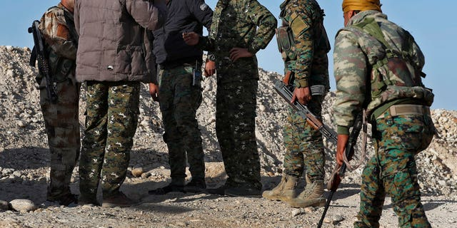 March 29: Commander Abu Ali Nejm, third from right, a leading member of the U.S-backed Syrian Manbij Military Council, speaks with his fighters at the front line against Turkish-backed fighters, at Halawanji village, north of Manbij town.