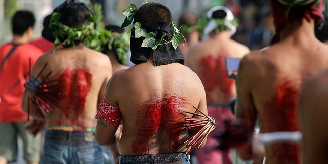 Filipino penitents line up as they flagellate during Good Friday rituals to atone for sins in San Fernando, Pampanga province, northern Philippines. The ritual is frowned upon by church leaders in this predominantly Roman Catholic country.