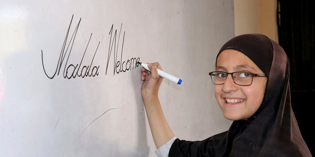 A Pakistani student of the school of Nobel Peace Prize winner Malala Yousafzai writes on a board writes on a board, in her hometown of Swat Valley in Pakistan, Friday, March 30, 2018.