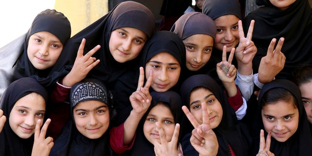 Students of the school of Nobel Peace Prize winner Malala Yousafzai flash victory sign in her hometown of Swat Valley in Pakistan, Friday, March 30, 2018.