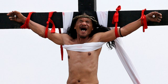 Ruben Enaje grimaces after gets nailed to the cross for the 32nd year in a row during a reenactment of Jesus Christ's sufferings as part of Good Friday rituals in the village of San Pedro Cutud, Pampanga province, northern Philippines.