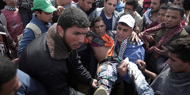 Palestinian protesters carry a wounded man during a demonstration near the Gaza Strip border.