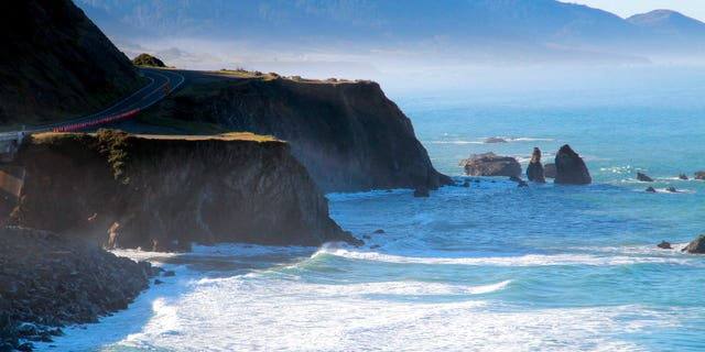 A helicopter hovers over steep coastal cliffs near Mendocino, Calif., where a vehicle plunged about 100 feet off a cliff.  (AP)