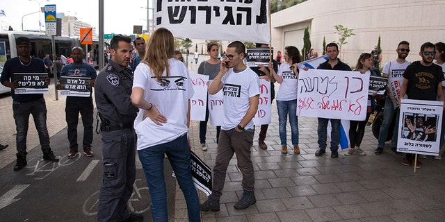 """Israel announced a deal with the U.N. on Monday to resettle African migrants in Western nations, but hours later put the agreement on hold. A protester carries a sign written in Hebrew reading """"Stop the deportation."""""""