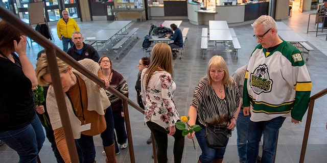 Humboldt Mayor Rob Muench, in the Broncos team jersey, along with other mourners lay down flowers on the stairs that enter to Elgar Petersen Arena, home of the Humboldt Broncos, on Saturday.
