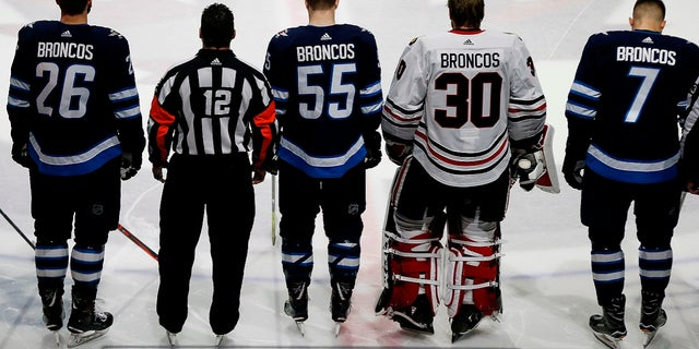"""Winnipeg Jets and Chicago Blackhawks players wear """"BRONCOS"""" on the back of their jerseys instead of their own names in a tribute to young players from Humboldt, Sask., who died in a bus crash, April 7, 2018."""