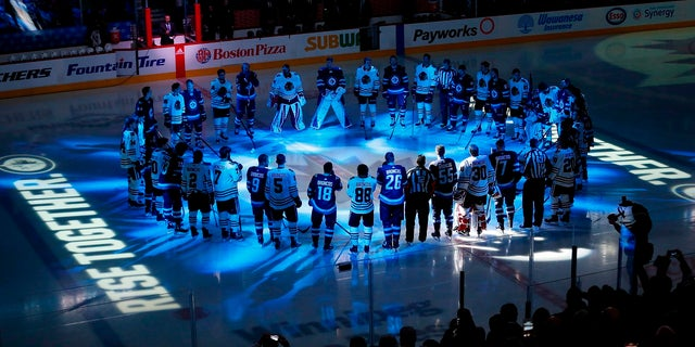Winnipeg Jets and Chicago Blackhawks players meet at center ice for a moment of silence for the Humboldt Broncos bus crash victims before a game in Winnipeg, Manitoba, April 7, 2018.