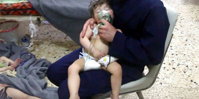 This image made from video released by the Syrian Civil Defense White Helmets shows a medical worker giving toddlers oxygen through respirators following an alleged poison gas attack.