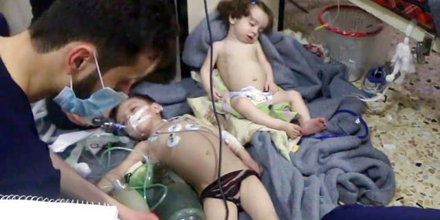 This image made from video released by the Syrian Civil Defense White Helmets shows medical workers treating toddlers following an alleged poison gas attack.