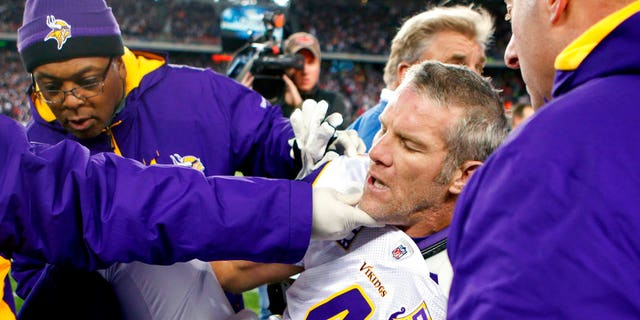 FILE 2010: Minnesota Vikings quarterback Brett Favre, center, is helped onto a cart to be taken off the field after a hit from New England Patriots' linebacker.