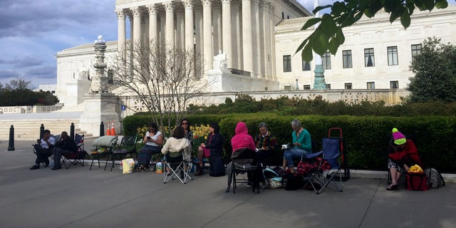 People wait in line outside the Supreme Court in Washington, to be in the gallery when the court hears arguments over President Trump's ban on travelers from several mostly Muslim countries.