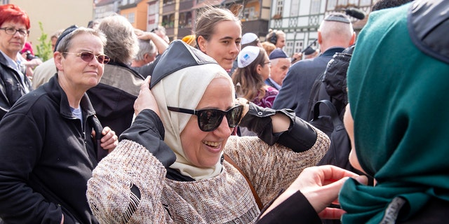 Muslim woman Samar Allaham, center, fixes the Jewish kippah on her head during a demonstration against antisemitism in Germany.