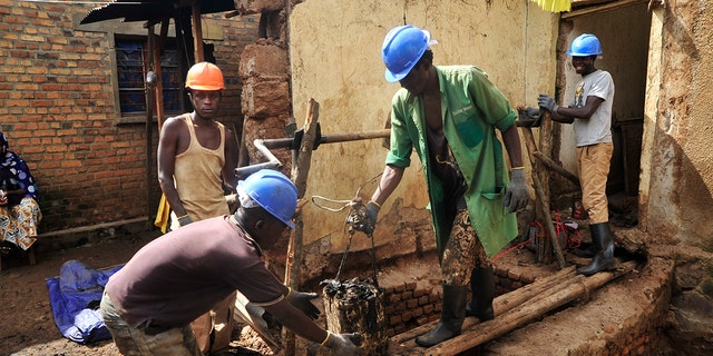 Residents excavate at the site of a recently-discovered mass grave in Gasabo district, near the capital Kigali, in Rwanda.
