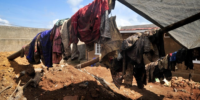 Clothes of genocide victims whose bodies were exhumed last week hang outside at the site of a recently-discovered mass grave in Gasabo district, near the capital Kigali, in Rwanda.