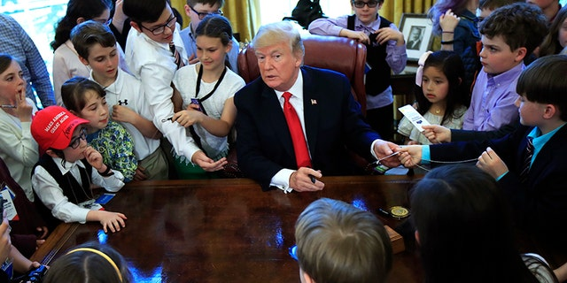 The kids crowded around the president's desk in the Oval Office for a photo.